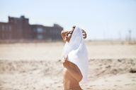 Woman with towel on head standing at beach against sky - CAVF07621