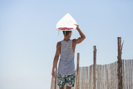 Man carrying surfboard on head while standing at beach - CAVF07630
