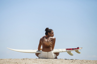 Rear view of woman with surfboard sitting at beach - CAVF07636