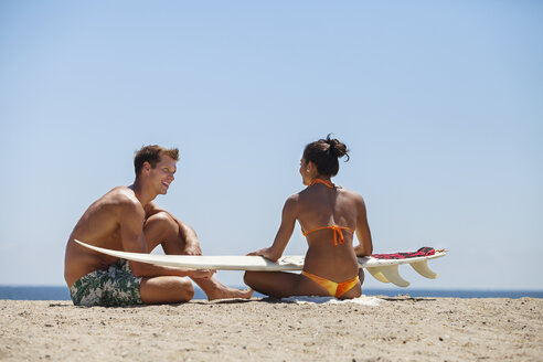 Happy couple talking while sitting on sand with surfboard - CAVF07639