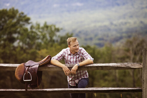 Happy rancher with saddle leaning on fence in farm - CAVF07654