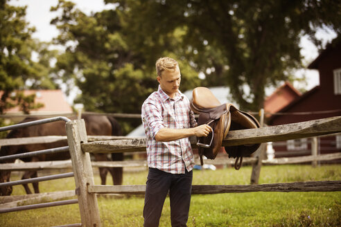 Rancher with saddle by fence in farm - CAVF07657