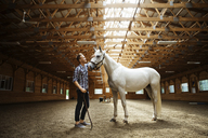 Side view of rancher stroking white horse in stable - CAVF07666