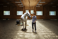 Rancher stroking white horse while standing in stable - CAVF07669