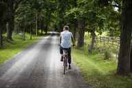 Rear view of man riding bicycle on road in forest - CAVF07675