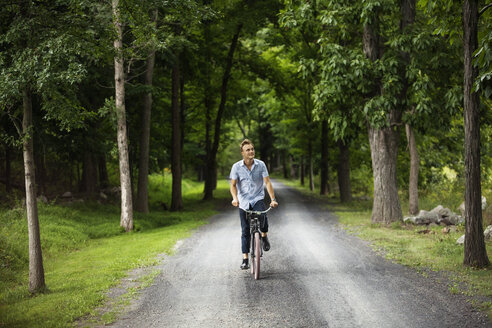 Happy man cycling on road in forest - CAVF07678