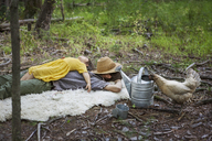 Family relaxing on blanket in forest - CAVF07711