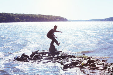 Side view of man balancing on rock in river against clear sky - CAVF07741