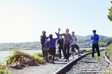Happy friends standing at railroad track against clear sky on sunny day - CAVF07744