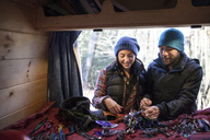 Couple looking at climbing equipment while standing by camper van - CAVF07795