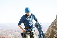 Man preparing for rock climbing while standing against sky - CAVF07813