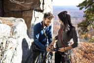 Man assisting girlfriend while rock climbing - CAVF07816