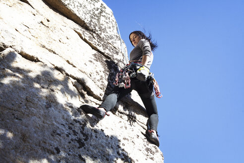 Low angle view of woman rock climbing against clear blue sky - CAVF07819