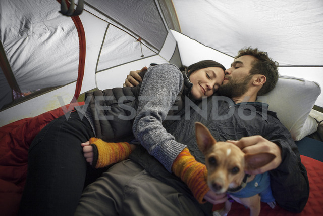 Man kissing girlfriend on forehead while relaxing in tent - CAVF07828