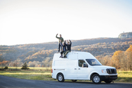 Happy friends with arms raised sitting on camper van - CAVF07834