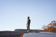 Man with hands in pocket standing on camper van against clear sky - CAVF07837