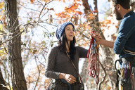 Boyfriend giving climbing equipment to girlfriend while standing by trees - CAVF07858