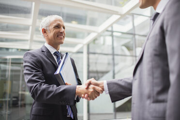 Businessmen shaking hands in office building - CAIF15753