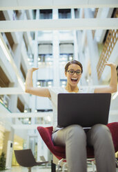 Businesswoman getting excited in office building - CAIF15756