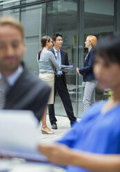 Business people talking outside of office building - CAIF15762