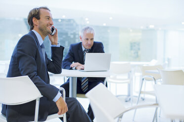 Businessman talking on call phone in office building cafe - CAIF15765
