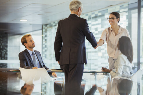 Business people shaking hands in office building - CAIF15771