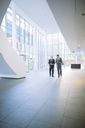 Businessmen walking together in office building - CAIF15774