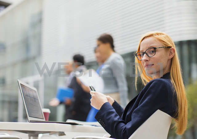 Businesswoman working at table outside of office building - CAIF15777