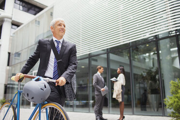 Businessman walking bicycle outside of office building - CAIF15780