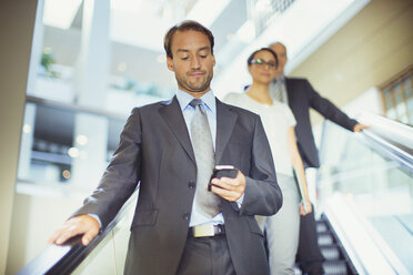 Businessman using cell phone on escalator in office building - CAIF15783