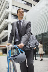Businessman walking bicycle outside of office building - CAIF15789