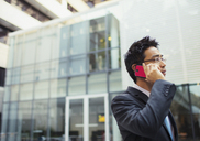 Businessman talking on cell phone outside of office building - CAIF15798