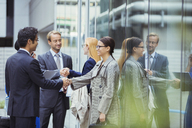 Business people shaking hands outside of office building - CAIF15801