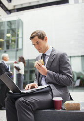 Businessman eat lunch and working outside office building - CAIF15804