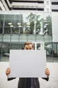 Businessman holding cardboard outside of office building - CAIF15828