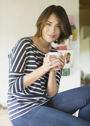 Portrait smiling brunette woman drinking coffee - CAIF15888