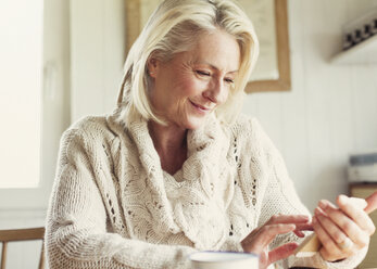 Smiling senior woman in sweater texting with cell phone in kitchen - CAIF15891