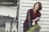 Portrait smiling brunette woman drinking coffee on porch - CAIF15894