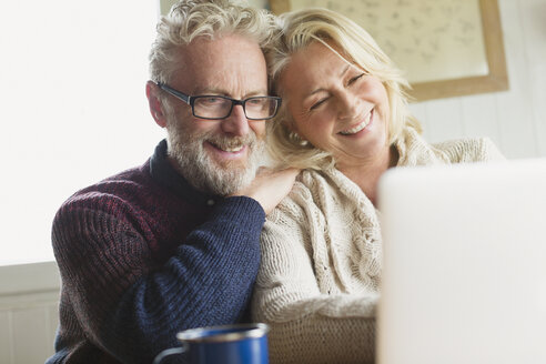 Smiling senior couple using laptop in kitchen - CAIF15900