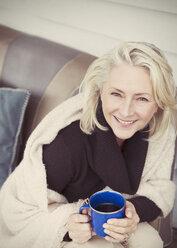 Portrait smiling senior woman wearing shawl drinking coffee on patio - CAIF15903