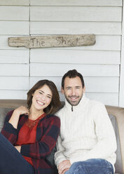 """Portrait smiling couple on porch below """"The Shack"""" sign - CAIF15915"""