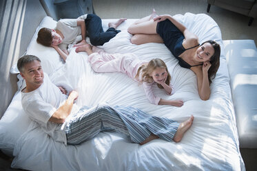 Portrait smiling family in pajamas relaxing on bed - CAIF15939