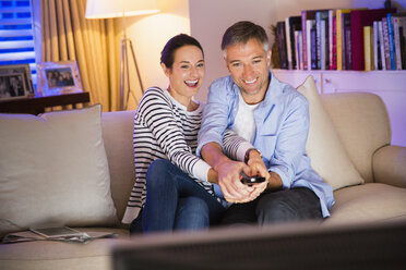 Playful couple fighting over remote control watching TV in living room - CAIF15945