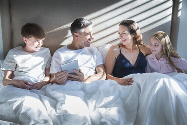 Smiling family laying in bed using digital tablet - CAIF15948