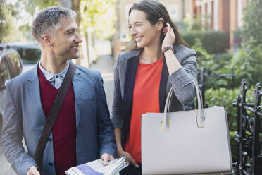 Business couple talking on morning sidewalk - CAIF15951