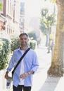 Portrait smiling businessman walking on sidewalk - CAIF15969