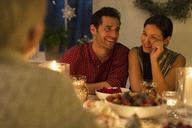 Smiling couple enjoying candlelight Christmas dinner - CAIF15975