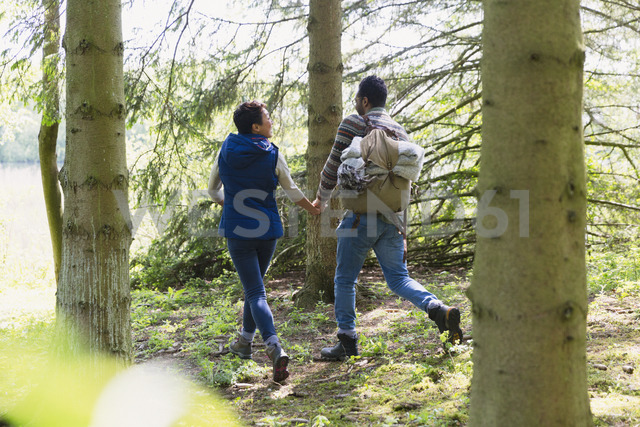Couple holding hands and hiking with backpack in woods - CAIF15999 - Sam Edwards/Westend61