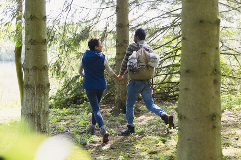 Couple holding hands and hiking with backpack in woods - CAIF15999