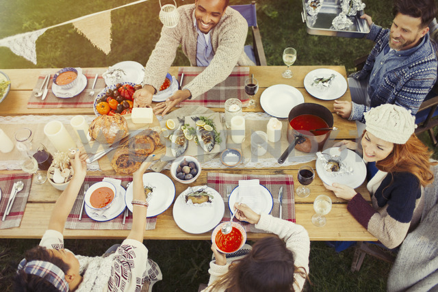 Friends enjoying lunch at patio table - CAIF16002